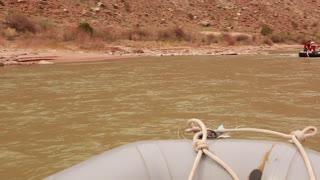 family rowing a river through a deep desert canyon