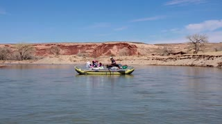 family rowing down a desert canyon river