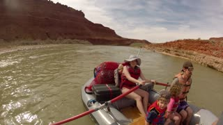 family rowing river raft on the san juan river on rafts