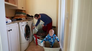 father doing the laundry with his toddler