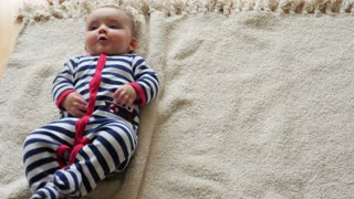 Father helps baby roll over on blanket
