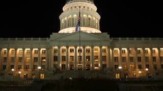 Flag flies at the amazing Utah State Capitol at night