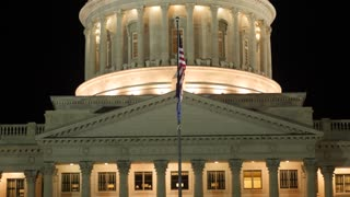 Flag flies at the Utah State Capitol at night