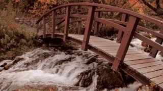 Footbridge over mountain river in the fall Dolly Shot