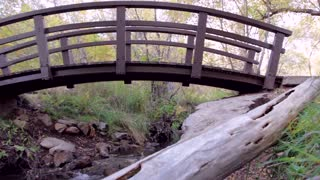 Footbridge over mountain stream dolly shot