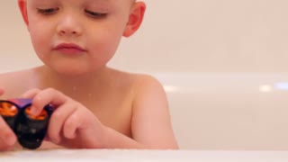 Fun little boy playing with a toy in his bathtub