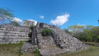 Gimbal shot of woman walking through mayan ruins at ek balam