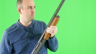 Green screen shot of a shooter with his shotgun at camera