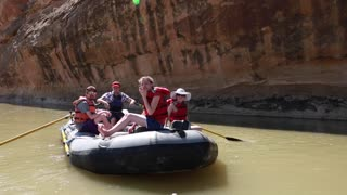 group rowing river rafts on san juan river by cliff