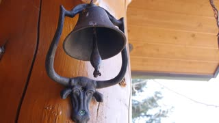 Hand rings a fun steer bell at the house