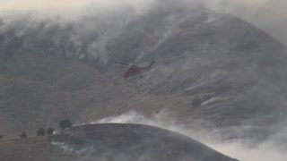 Helicopter Dropping Water on Large Wildfire