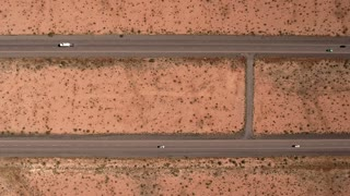 High aerial shot cars and trucks traveling on highway in a desert