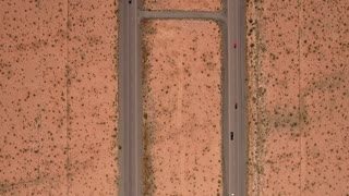 High aerial shot cars traveling on highway in a desert