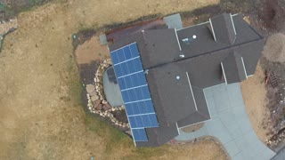 High aerial shot of a home with solar panels on roof in spring
