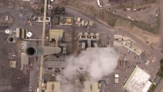 High aerial shot of a large coal power plant smoke stack