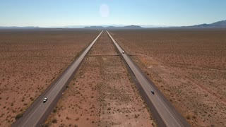 High aerial shot of vehicles on a long straight highway in a desert