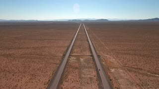 High aerial shot of vehicles on long straight highway in a desert