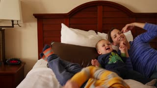 Interior dolly shot of a family on hotel room bed