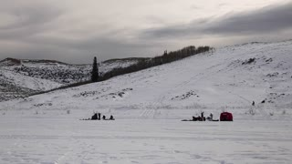 Kids sled down hill while families ice fish panning shot