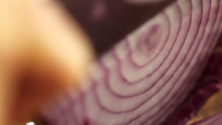 knife slicing a red onion close up