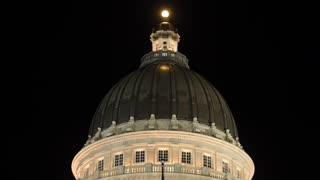 Lights on the Utah State Capitol dome with flags tilting shot
