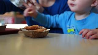 little boy eating chicken strips