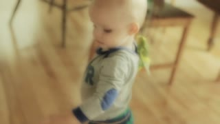 little boy playing in his kitchen with parakeet