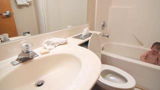 Little boy playing in hotel room bath tub panning shot