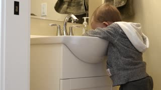 Little boy washing his hands in the bathroom