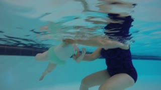 Little girl playing in swimming pool with mother