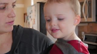 Little toddler blows nose into kleenex