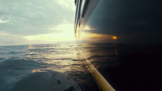 Low shot of a large fishing boat in ocean with sunset