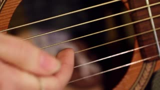 Macro of plucking guitar strings