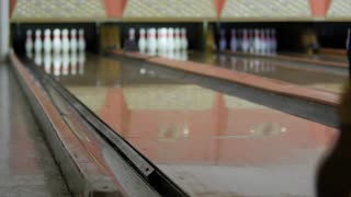 Man hits pins with bowling ball in bowling alley