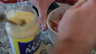 man mixes mayonnaise into a tuna fish sandwich