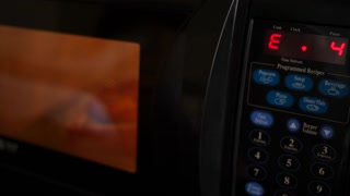 Man removes microwave pizza in a hotel room