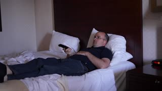 Man rests on a hotel bed and watches TV