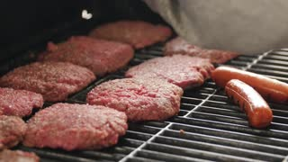 Man seasoning hamburgers and hot dogs on grill