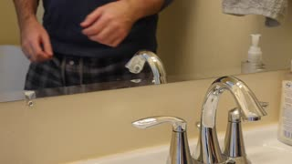 Man washes his hands in the bathroom in mirror