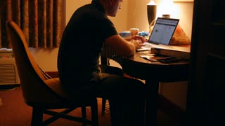 Man working in dark hotel room at night on computer gets up