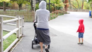 Mother and a boy with stroller at the zoo gimbal shot
