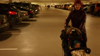 Mother and toddler push baby in stroller through parking garage