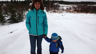 mother and toddler walking through snowy forest