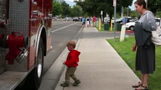 Mother watches son touch a fire engine