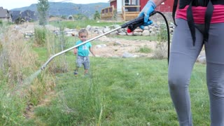 Mother with a toddler sprays weeds with weed killer in yard