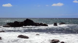 Ocean waves crash along the rocky shoreline