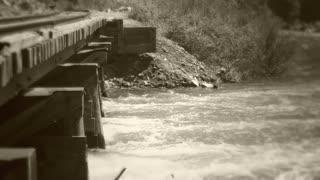 Old train bridge over flooding river