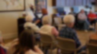 Out Of Focus Shot Of People Listening To Piano In Retirement Home