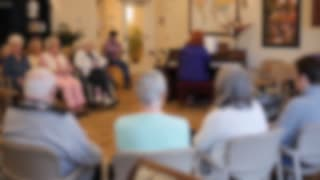 Out Of Focus Shot People Listening To A Piano In Retirement Home