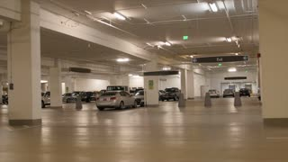 People and cars in empty parking garage